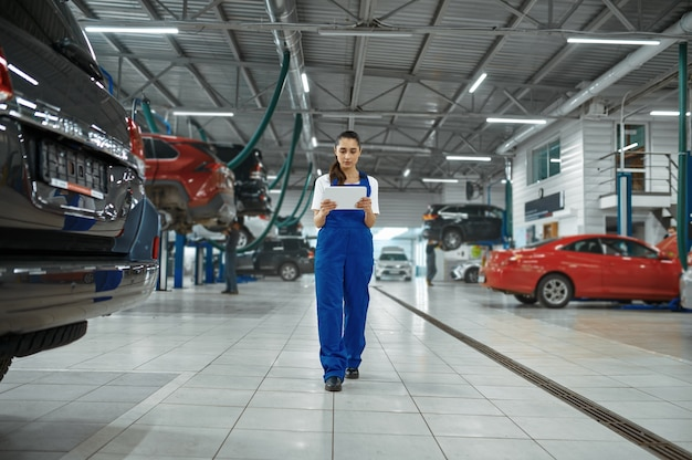 Monteur vrouw met laptop in mechanische werkplaats, professionele diagnose