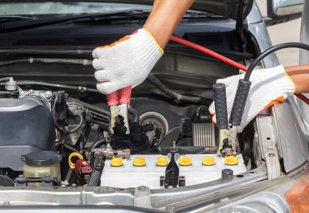 Monteur werkt in auto reparatiewerkplaats.