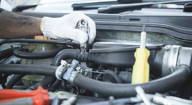 Monteur werkt in autoreparatie. hand van automonteur met moersleutel