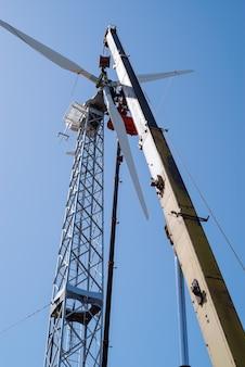 Monteurs gebruiken vrachtwagenkraan en hoogwerker om windturbinerotor te installeren