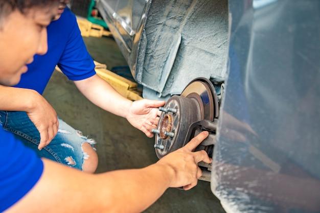 Monteurs in uniform werken in de autoservice met het verwijderen van wiel en chassis.