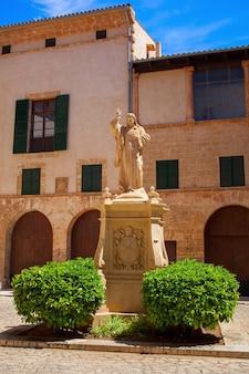 Monument in palma de mallorca met twee groene struiken dichtbij