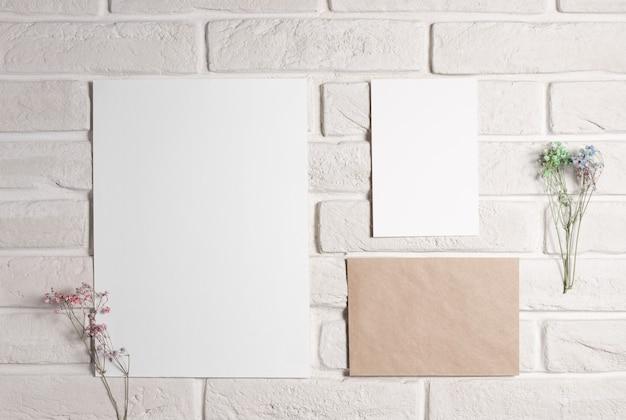 Moodboard-sjabloon met blanco papieren kaarten op witte bakstenen muur met gedroogde bloemen