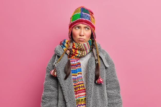 Moody ontevreden aziatische vrouw geconcentreerd ergens met beledigde uitdrukking draagt gebreide muts sjaal en grijze bontjas poseert tegen roze studiomuur