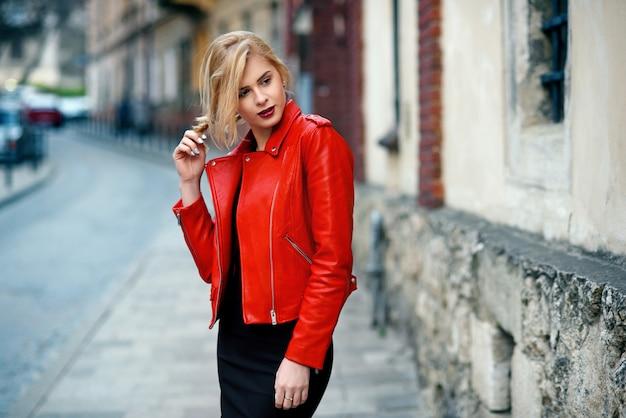 Mooi aantrekkelijk blond meisje met ideale figuur in een rode leren jas en strakke zwarte rok raakt haar hand aan haar haar bij zonsondergang
