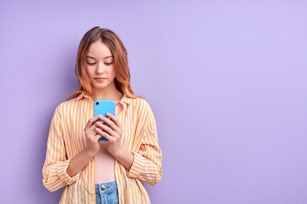 Mooi aantrekkelijk mooi charmant schattig vrolijk vrolijk gericht meisje met behulp van mobiele webapp geïsoleerd op paars