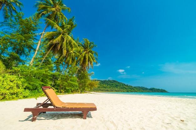 Mooi aard tropisch strand en overzees met stoel en kokosnotenpalm op paradijseiland