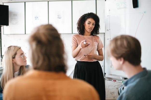 Mooi afrikaans amerikaans meisje met donker krullend haar dat zich dichtbij raad bevindt en presentatie geeft aan collega's in bureau