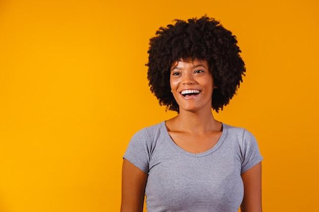 Mooi afrikaans amerikaans meisje met een afro kapsel glimlachen. Premium Foto