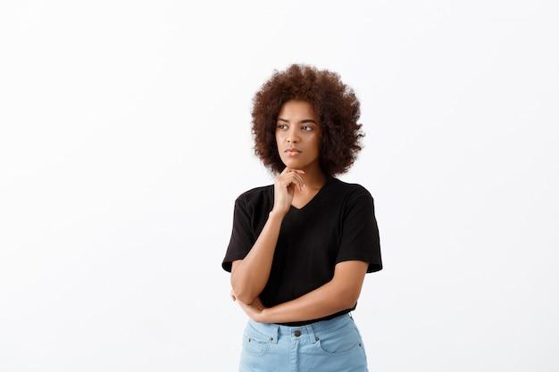 Mooi afrikaans meisje dat over lichte muur denkt.