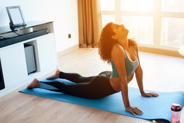 Mooi afrikaans meisje dat yogaoefeningen op een yogamat doet