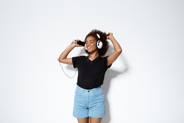 Mooi afrikaans meisje luisteren muziek in hoofdtelefoons over witte muur.