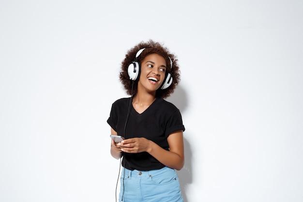 Mooi afrikaans meisje luisteren muziek in hoofdtelefoons over witte muur