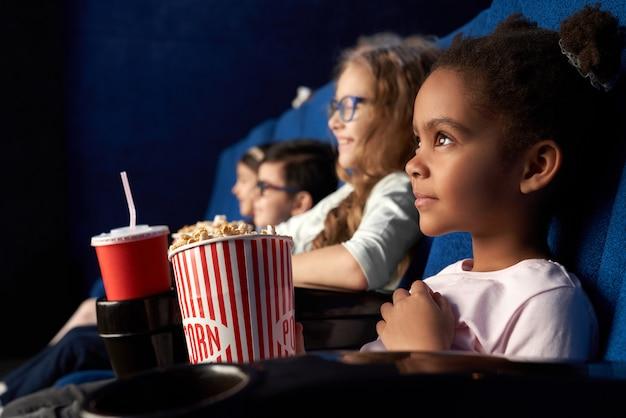 Mooi afrikaans meisje met grappige kapsel kijken naar film in de bioscoop