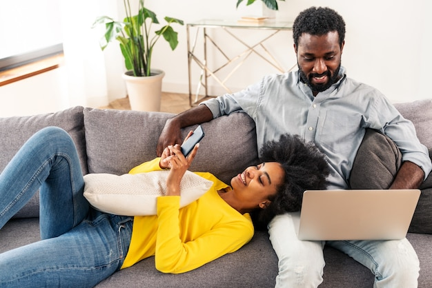 Mooi afro-amerikaans echtpaar dat op een computerlaptop werkt - modern paar dat online winkelt