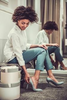 Mooi afro-amerikaans meisje probeert schoenen met hoge hakken.