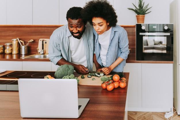 Mooi afro-amerikaans paar dat thuis kookt mooi en vrolijk zwart paar dat diner voorbereidt