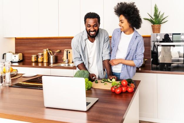 Mooi afro-amerikaans paar dat thuis kookt mooi zwart paar dat diner voorbereidt