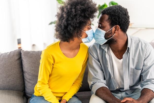 Mooi afro-amerikaans stel dat thuis knuffelt en een beschermend gezichtsmasker draagt tijdens covid-19 pandemische quarantaine