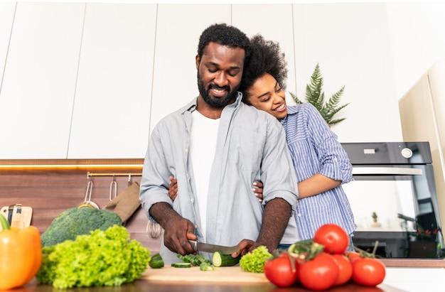 Mooi afro-amerikaans stel dat thuis kookt - mooi en vrolijk zwart stel dat samen in de keuken het diner bereidt