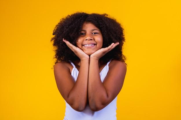 Mooi afro meisje op gele achtergrond met vrije ruimte voor tekst. afro kind op gele achtergrond