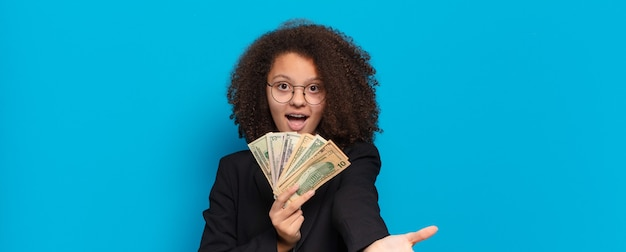 Mooi afro-tiener bedrijfsmeisje met dollarbankbiljetten