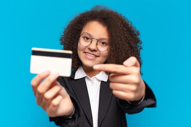 Mooi afro-tiener bedrijfsmeisje met een creditcard. online winkelconcept