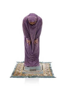 Mooi arabisch meisje bidden op een mat