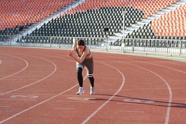Mooi atletisch meisje dat rond het stadion loopt