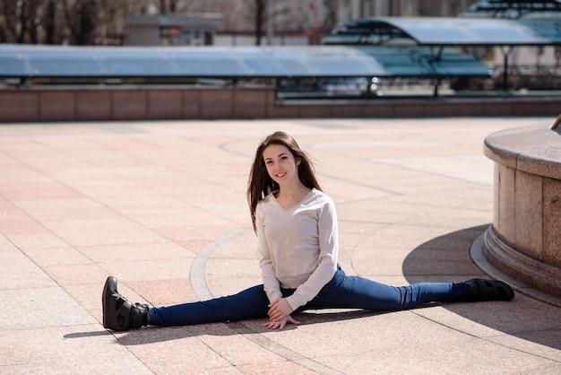 Mooi atletisch meisje dat zich uitstrekt in de stad