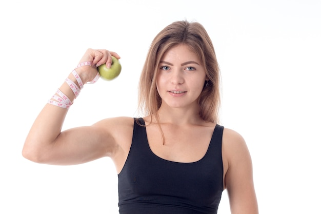 Mooi atletisch meisje toont spieren die een appel in zijn hand balden en direct wissen