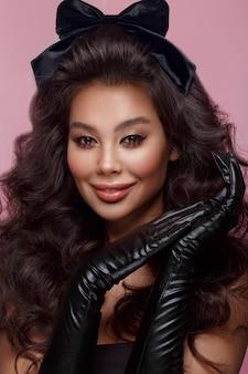 Mooi aziatisch donkerbruin model met volumekrullen, klassieke make-up en sexy lippen
