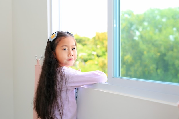 Mooi aziatisch klein jong geitjemeisje die thuis bij venster van huis liggen.
