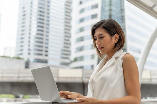 Mooi aziatisch meisje dat in bedrijfsvrouwenkleren glimlacht die laptop computer en smartphone met behulp van