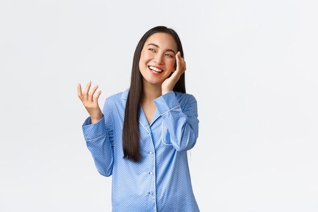 Mooi aziatisch meisje dat zich klaarmaakt om te slapen, zacht schoon gezicht aan te raken na het aanbrengen van huidverzorgingsproducten voor de nacht, pyjama's dragen, lachen en kijken linkerbovenhoek blij, witte muur