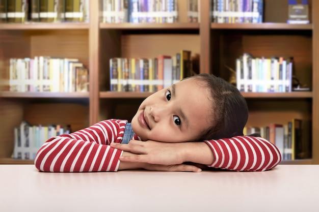 Mooi aziatisch meisje die op bureau het rusten liggen