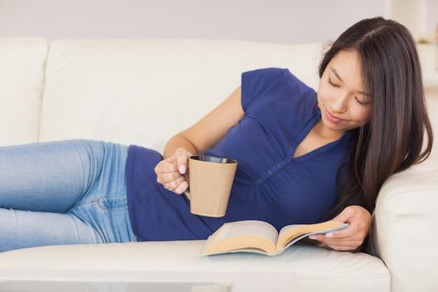 Mooi aziatisch meisje die op de bank liggen die een roman lezen en hete drank drinken