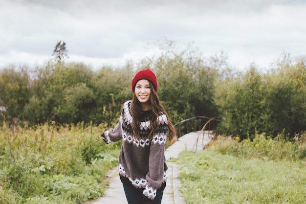 Mooi aziatisch meisje die yellredowhoed en gebreide sweater in de herfstpark dragen
