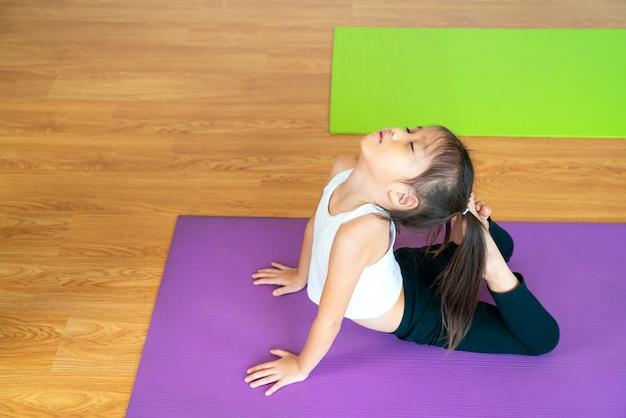 Mooi aziatisch meisje doet yoga vormt workout oefening om thuis te ontspannen en te mediteren. azië, yoga, zen, sport, fitness. gezond, thuisactiviteit of aziatisch vrouwenconcept