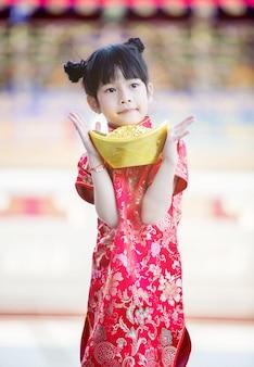 Mooi aziatisch meisje draagt rode cheongsam en houdt chinese goudstaaf voor de marmeren trappen van de prachtige chinese tempel voor chinees nieuwjaar