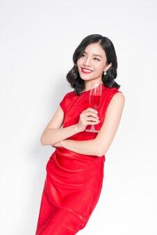 Mooi aziatisch meisje in avondjurk glimlachend met glas champagne