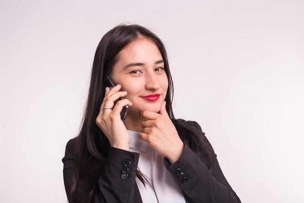 Mooi aziatisch meisje in formele kleding met telefoon op witte muur