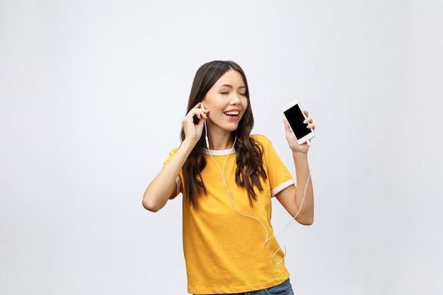 Mooi aziatisch meisje met professionele make-up en stijlvol kapsel zingen en dansen tijdens het luisteren naar muziek