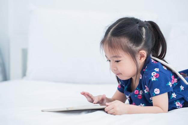 Mooi aziatisch meisjesjong geitje die tabletcomputer met behulp van