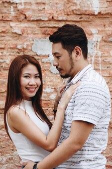 Mooi aziatisch paar door een bakstenen muur