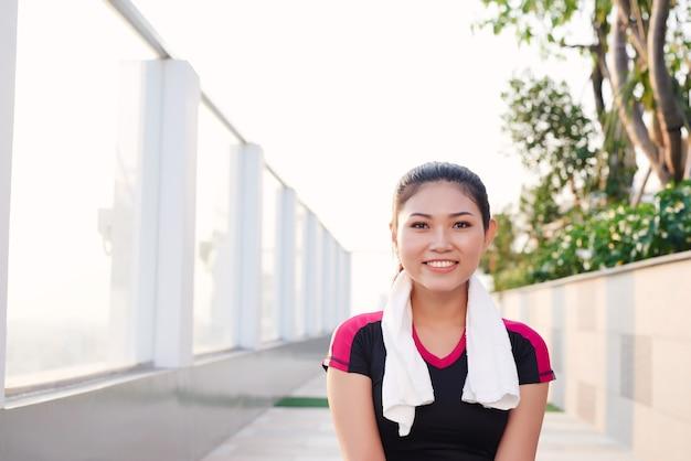Mooi aziatisch sportief meisje dat lacht terwijl ze in het park zit.