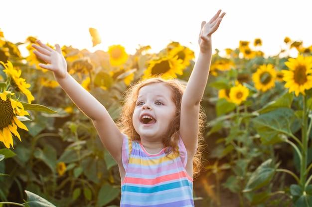 Mooi babymeisje dat in de zonnebloemen staat en handen opsteekt