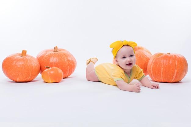 Mooi babymeisje in een geel lichaam met een gele strik op haar hoofd