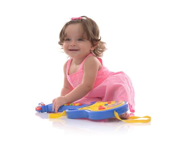 Mooi babymeisje met stuk speelgoed gitaar