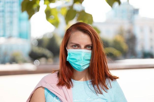 Mooi bang meisje in een medisch beschermend masker in een park